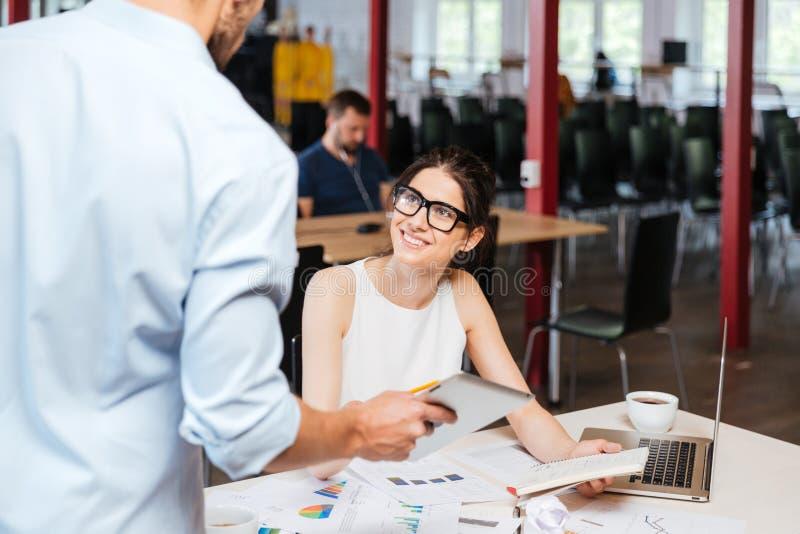 快乐的女商人谈话与有片剂的同事在办公室 免版税图库摄影