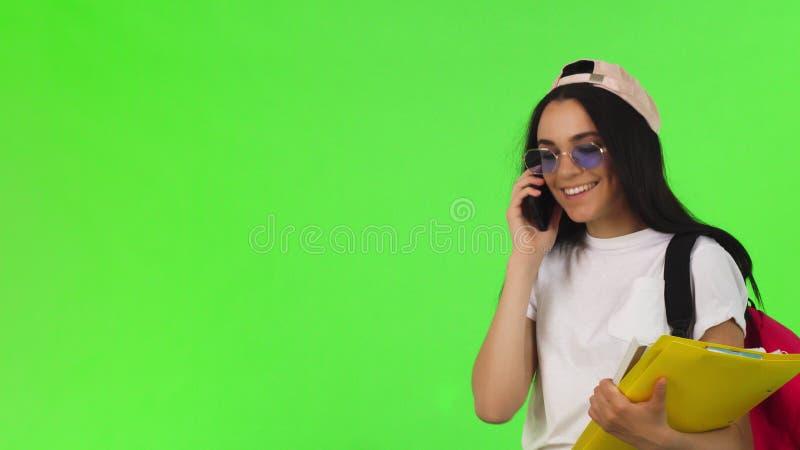 快乐的女学生谈话在电话,拿着她的书 免版税库存照片