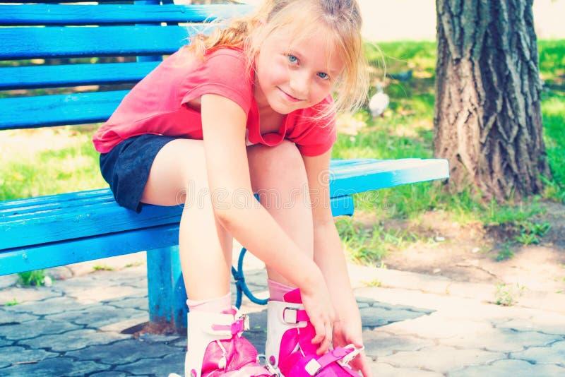 快乐的女孩、红颜色白肤金发的衣裳路辗和看看照相机和微笑,在公园坐一条蓝色长凳 免版税库存照片