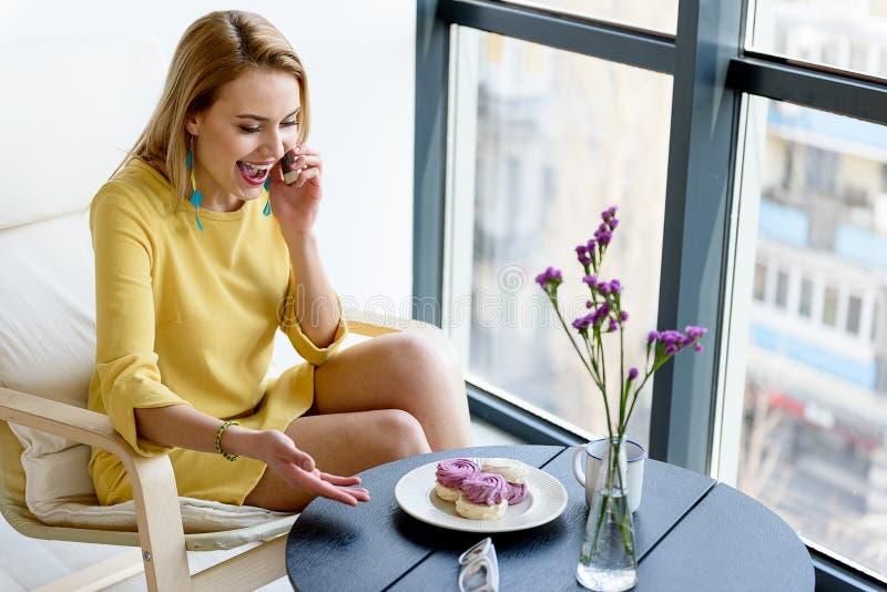 快乐的女孩谈话在充满喜悦的智能手机 免版税库存图片