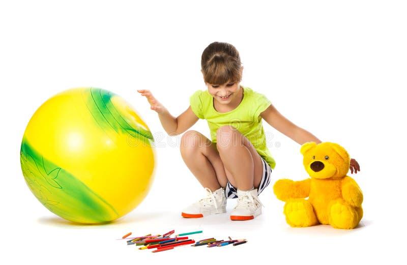 快乐的女孩画铅笔和玩具 免版税库存图片