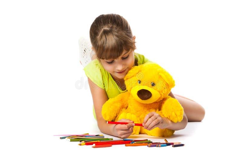 快乐的女孩画铅笔 图库摄影