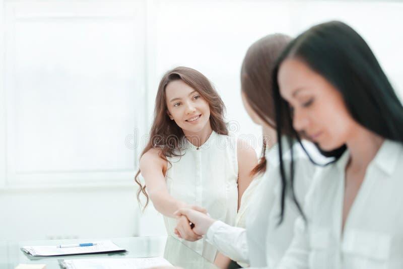 快乐的女实业家和客户握手,坐在桌上 免版税图库摄影