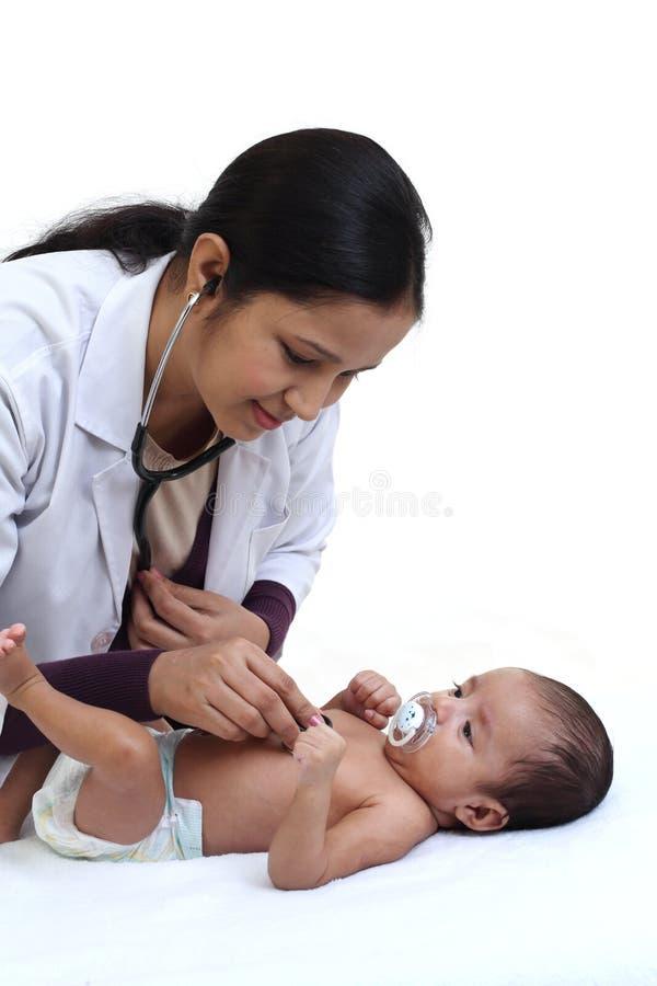 快乐的女性儿科医生抱着新出生的婴孩 免版税图库摄影