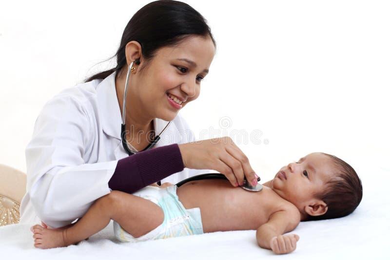快乐的女性儿科医生抱着新出生的婴孩 免版税库存照片