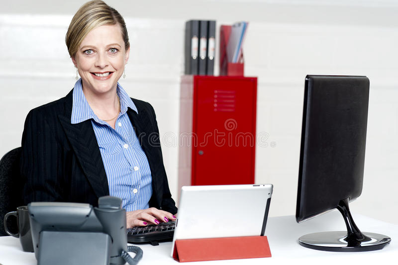快乐的女性秘书键入的文件 免版税图库摄影