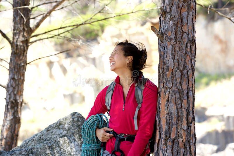 快乐的女性远足者支持的树和看  免版税库存照片