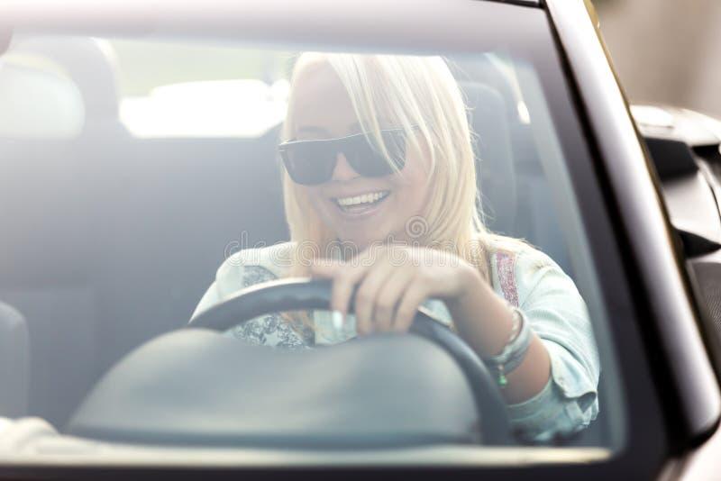 年轻快乐的妇女乘坐的敞篷车 库存照片