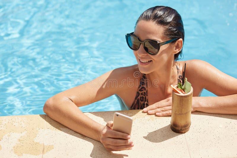 快乐的妇女佩带的游泳场和黑太阳镜,获得乐趣和沐浴在旅馆手段温泉水池,饮用的新鲜的鸡尾酒 免版税库存照片