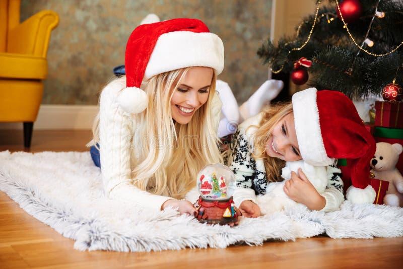 快乐的妇女和小女孩圣诞老人使用与雪的` s帽子的 免版税库存图片