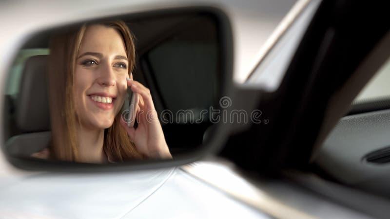 快乐的妇女坐在汽车和谈话在有父母的智能手机 免版税库存图片