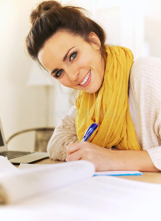 在她的学报的快乐的妇女文字 免版税图库摄影