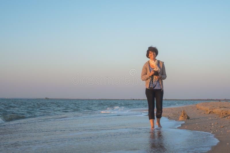 快乐的妇女沿与照相机的海滩走 库存照片