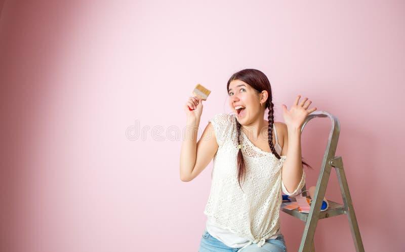 快乐的妇女照片有刷子的在活梯和路辗旁边对空白的桃红色墙壁 免版税图库摄影