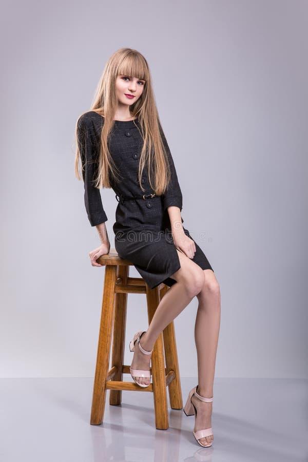 快乐的妇女画象坐椅子和看在灰色背景的黑礼服的照相机 免版税库存照片