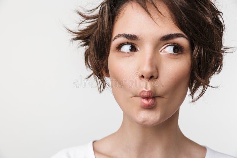 快乐的妇女画象特写镜头有短的棕色头发的在做鱼的基本的T恤杉面对与嘴唇在照相机 免版税图库摄影