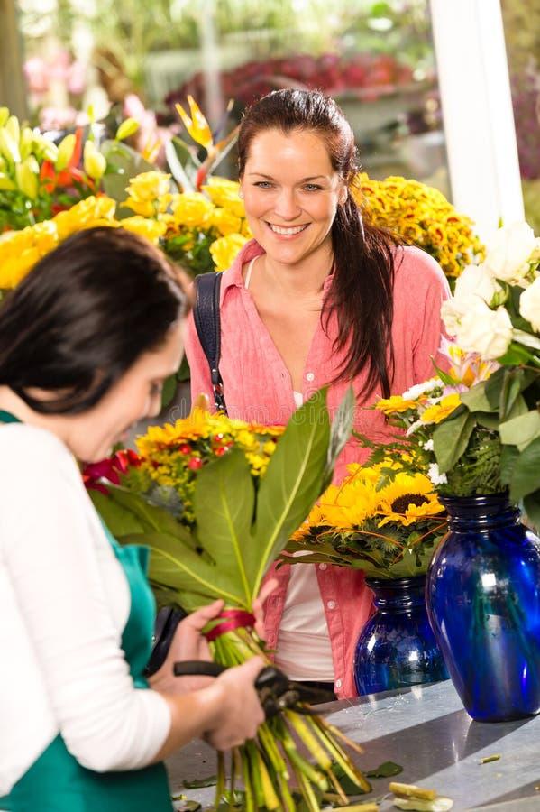 快乐的妇女采购的花束花店卖花人 库存照片