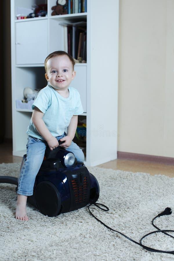 快乐的婴孩备鞍了吸尘器,当清洗屋子和愉快地微笑时 库存图片