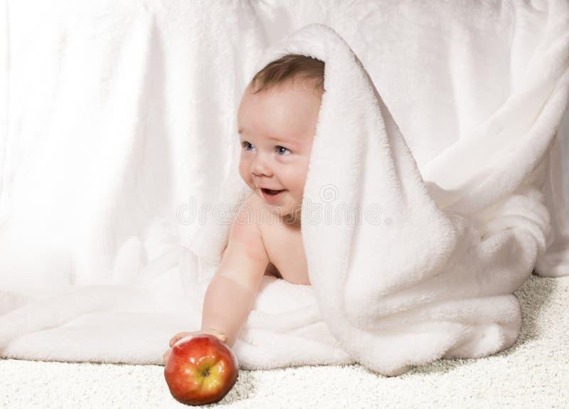 快乐的婴孩用在一条空白毯子之下的红色苹果 免版税库存照片