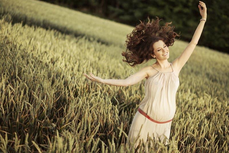 快乐的孕妇的画象在谷物庄稼中的 库存照片