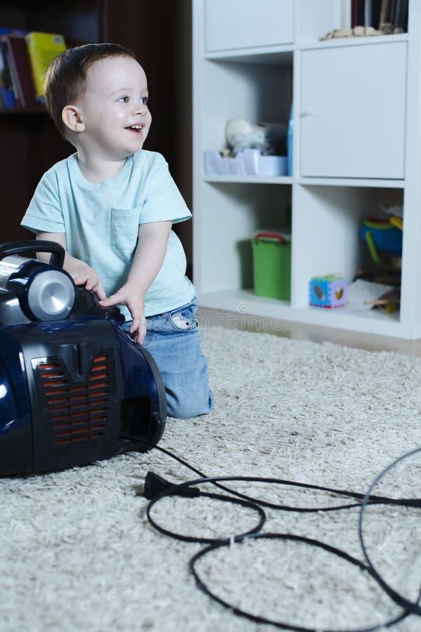 快乐的孩子取消吸尘器和愉快地微笑的绳子 免版税图库摄影