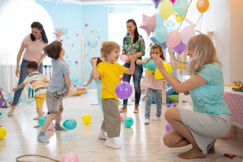 快乐的孩子和他们的父母愿意考虑并且获得与颜色气球的乐趣在生日宴会 免版税库存图片