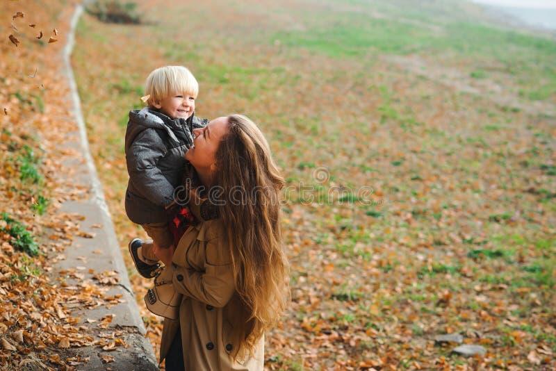 快乐的孩子妈妈在秋天散步时玩笑 年轻家庭秋散 妈妈和她的小儿子 库存照片