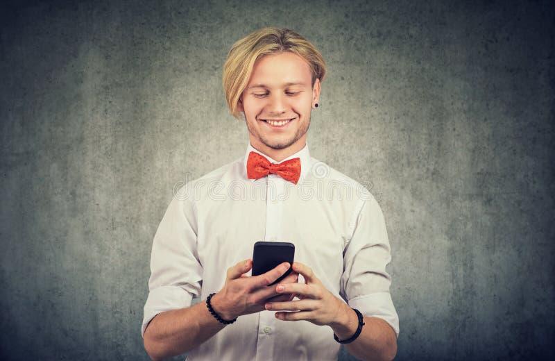 快乐的家伙用他的智能手机 免版税库存照片
