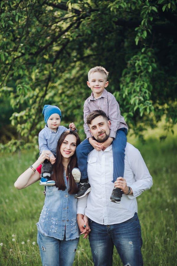 快乐的家庭,获得乐趣户外,看照相机和摆在夏天公园 库存照片