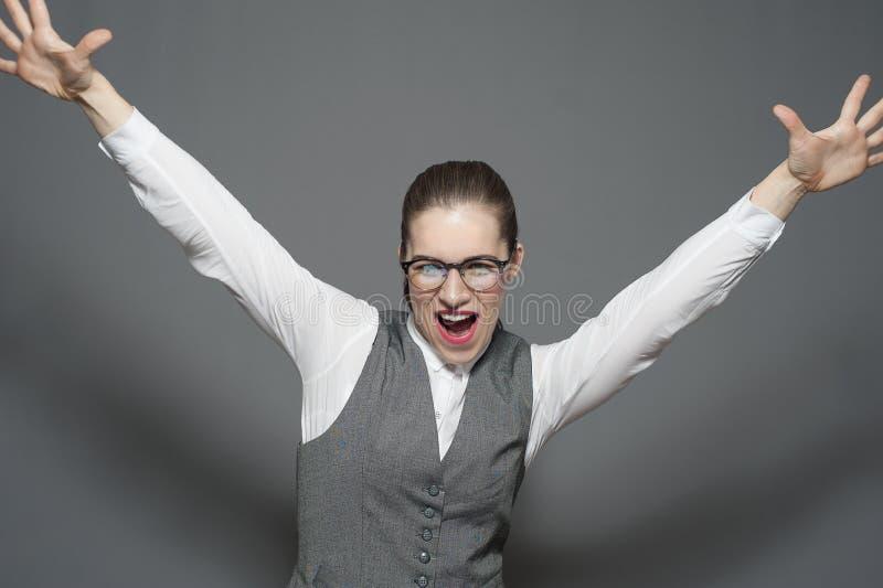 快乐的对天空的女实业家站立的手 库存图片