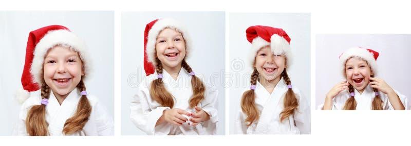 快乐的小女孩与圣诞老人童帽的四年在他的头 库存照片