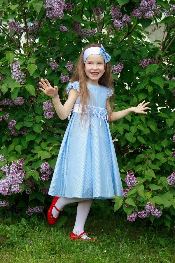 快乐的小女孩在丁香的灌木站立 库存图片