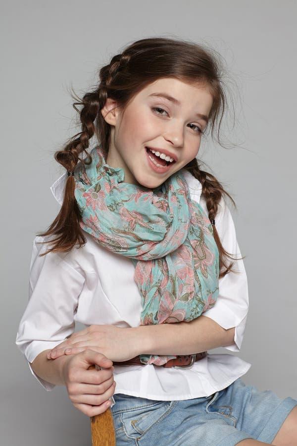 笑的小女孩坐椅子 免版税库存图片
