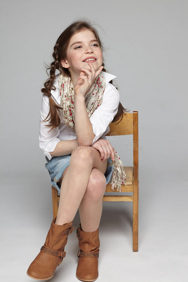 快乐的小女孩坐椅子 库存图片