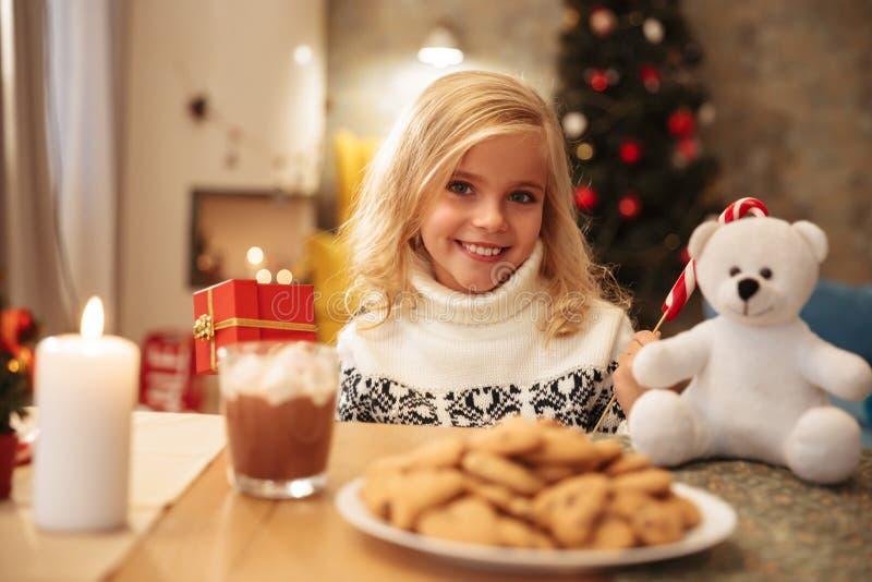 快乐的小女孩拿着礼物的和坐在w的棒棒糖 图库摄影