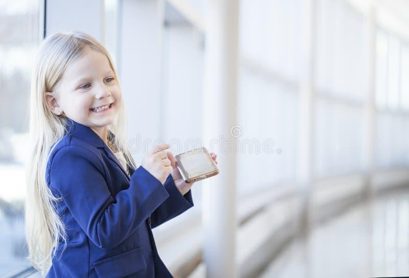 快乐的小女孩画象水兵的有智能手机的 免版税库存照片