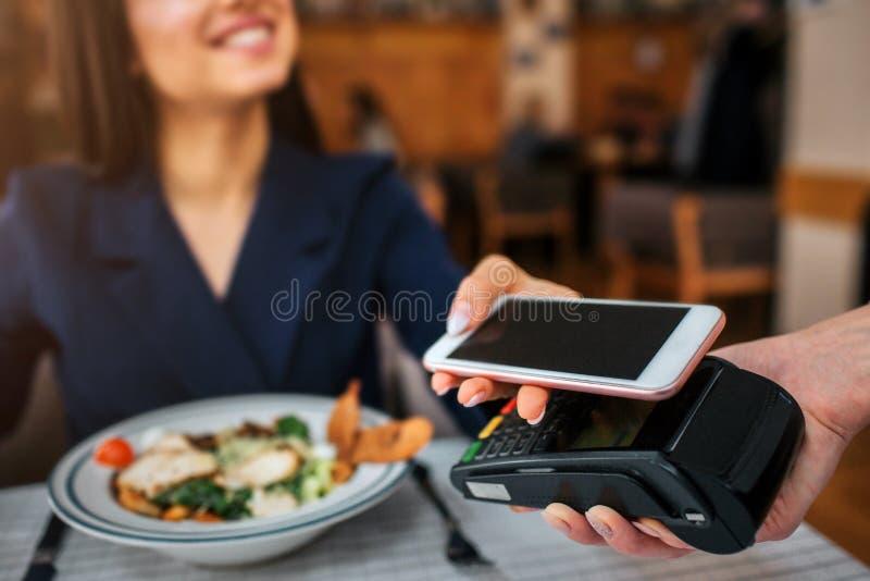 快乐的小家伙坐在桌和神色上在女服务员 她微笑 在终端的式样举行电话 她支付午餐 免版税库存照片