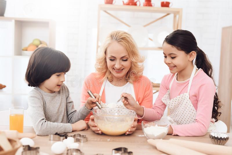 快乐的小男孩搅拌在碗的鸡蛋用牛奶,并且她的姐妹倒面粉 库存照片