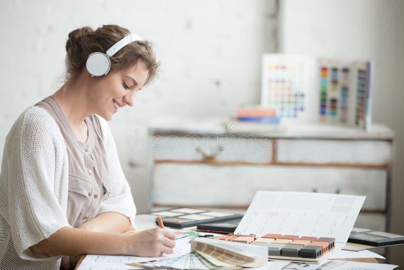 快乐的少妇听的音乐在工作 免版税图库摄影