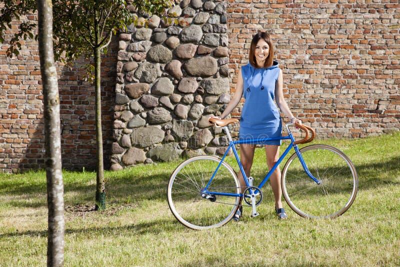 快乐的少妇和老牌骑自行车赛跑 免版税库存图片