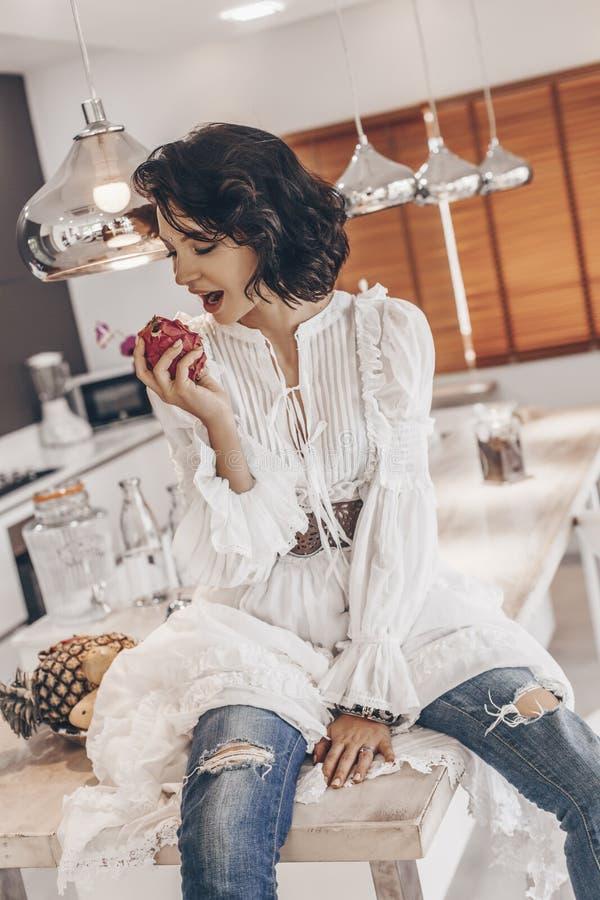 快乐的少妇坐在别墅和吃的厨房书桌 库存图片