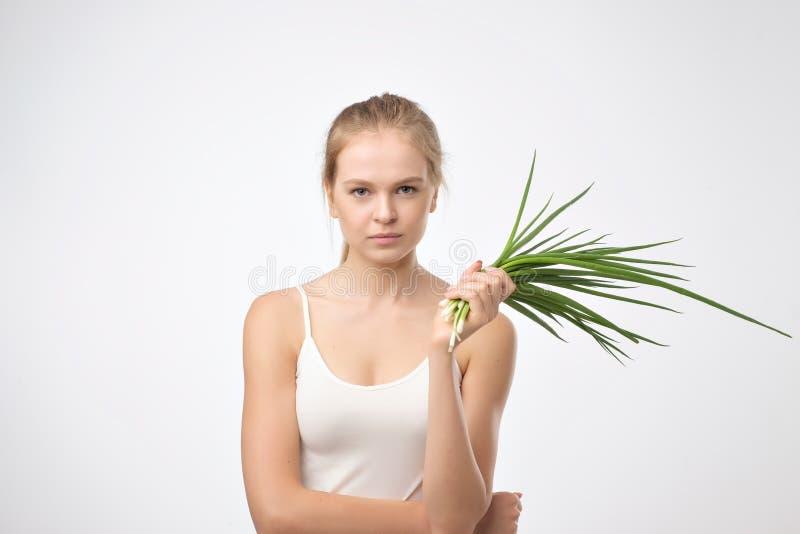 快乐的少妇用葱 健康的食物 免版税库存照片