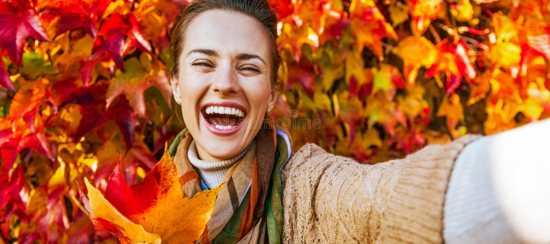 快乐的少妇画象有秋天的生叶做selfie 库存照片