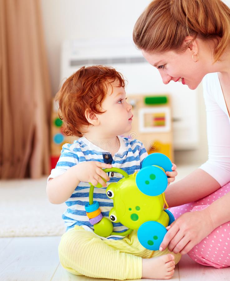 快乐的少妇,打与孩子的母亲比赛在托儿所室 免版税库存图片