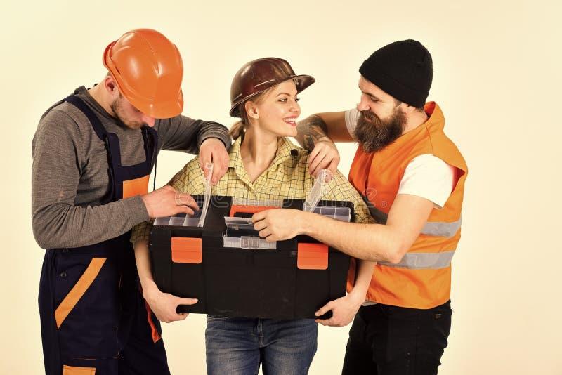 快乐的工作者公司,建造者,修理匠,石膏工 男人和妇女有微笑的面孔的在盔甲和boilersuit 免版税库存图片