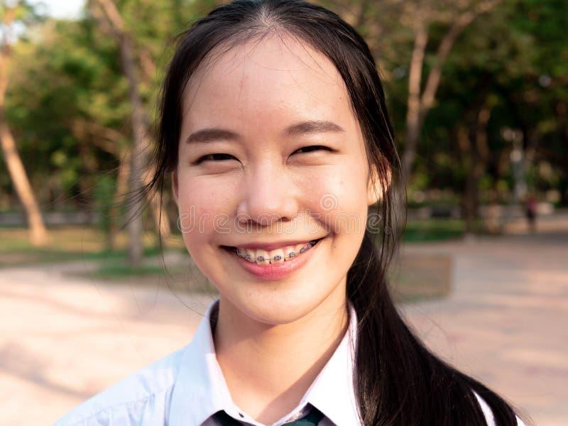 快乐的年轻亚洲女孩感觉愉快微笑肯定她自己,当旅行在街道上时 生活方式假日概念,看 免版税图库摄影