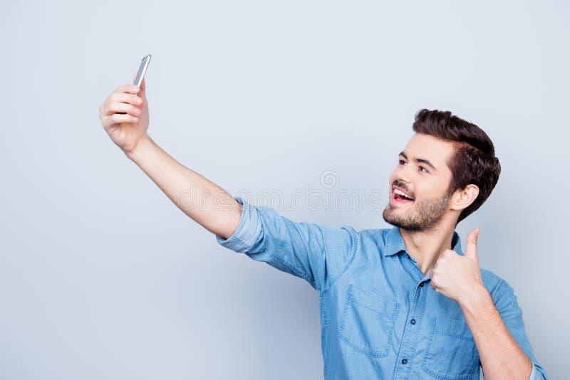 快乐的年轻人在他的电话a照相机做selfie  免版税库存照片