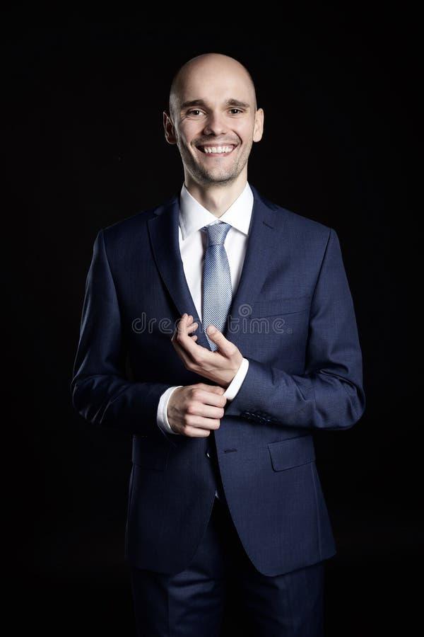快乐的年轻商人定象打他的衣服 免版税库存照片