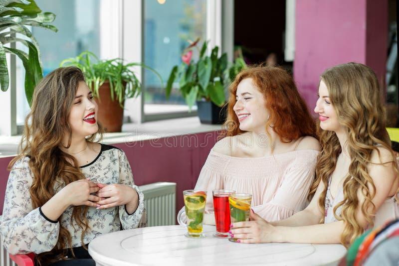快乐的年轻女人在咖啡馆聊天 笑 友谊,会面 库存照片