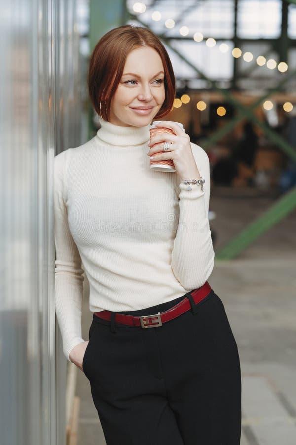 快乐的年轻女人照片穿典雅的衣裳,穿戴在白色套头衫,并且黑长裤,喝一次性咖啡, 免版税库存图片
